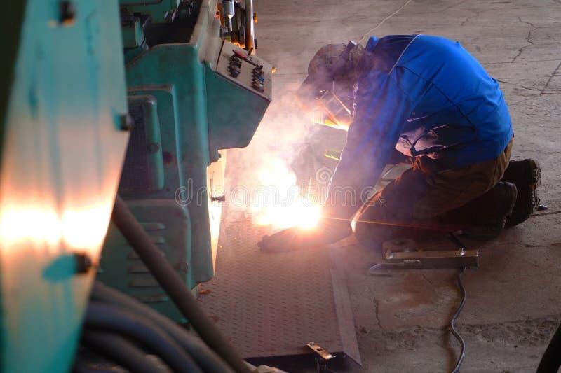 El soldador en la planta industrial hace la conexión usando un arco voltaico imagen de archivo libre de regalías