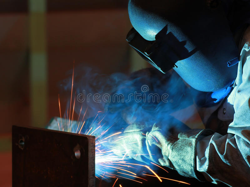 El soldador está soldando con autógena la estructura de acero con todo el equipo de seguridad en fábrica fotografía de archivo