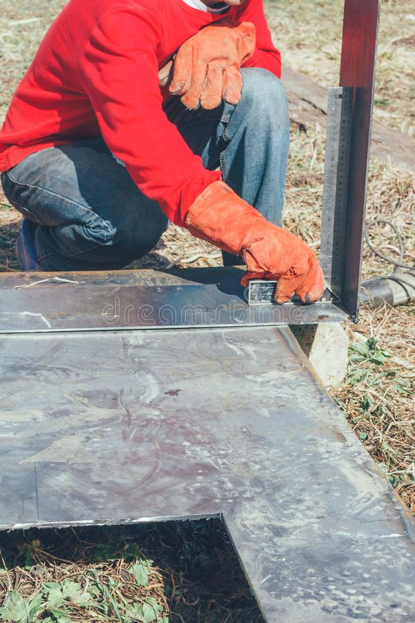 El soldador hace medidas del corchete menor/mayor de acero de la regla de las piezas de metal imagen de archivo libre de regalías