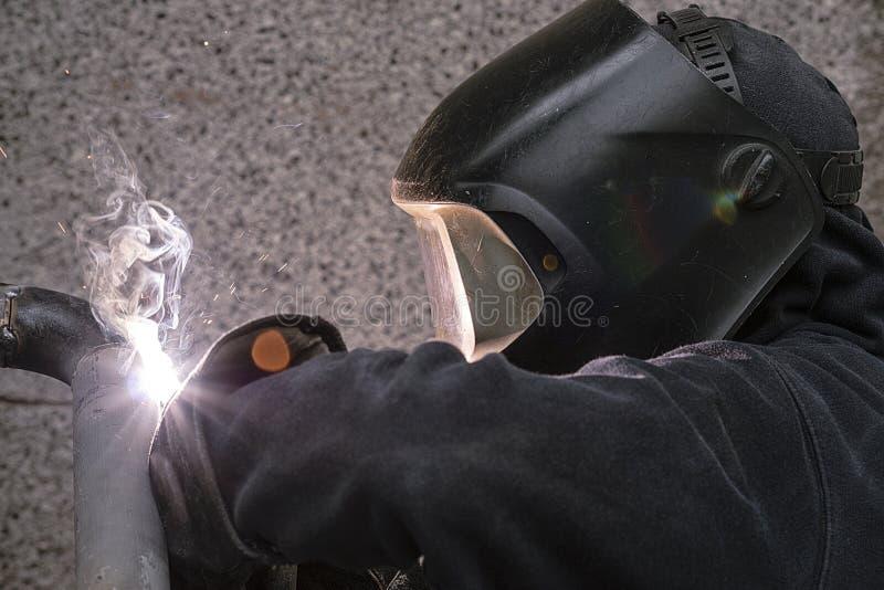 El soldador suelda con autógena los tubos para la instalación del gas imagen de archivo