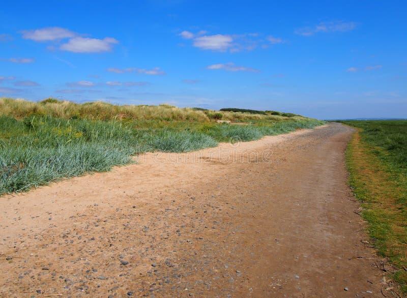 El solo camino de tierra de la tierra hecho de la arena y de las piedras que extendían a la distancia con la hierba cubrió las du imagen de archivo libre de regalías