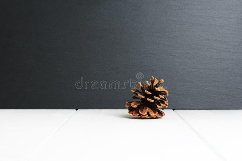 El solo cono del pino en la superficie de madera blanca y la pizarra negra empiedran el fondo imagen de archivo