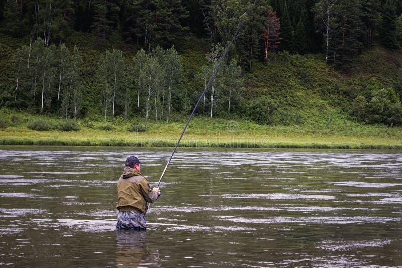 El solo pescador en un río tranquilo es pesca del otoño imagenes de archivo