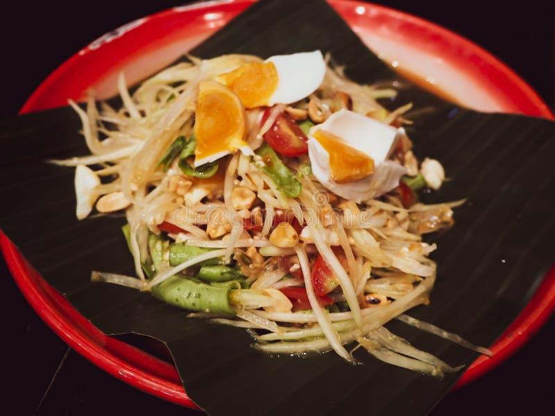 El som Tam Thai Green Papaya Salad sobre servicio de la hoja del plátano con el huevo el mejor menú delicioso delicioso de la com fotos de archivo libres de regalías