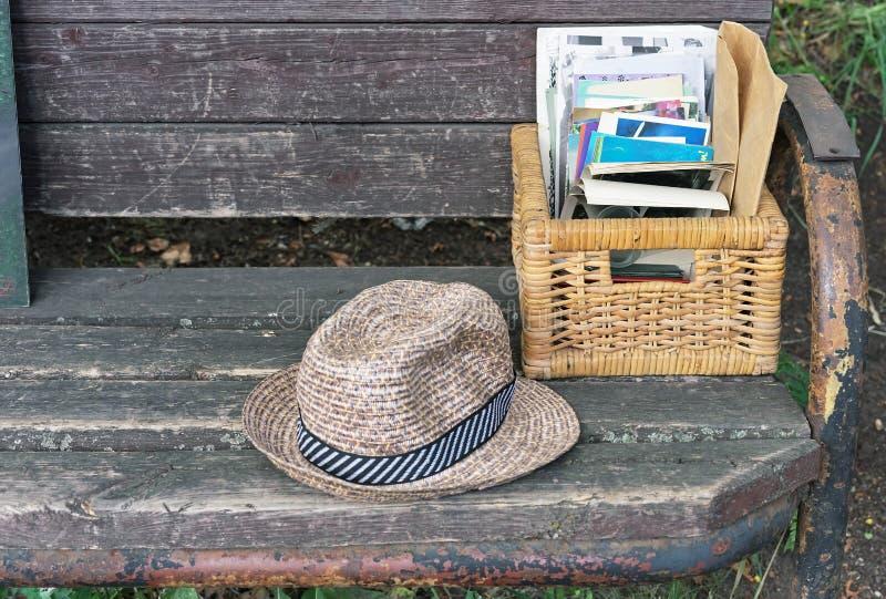 El sombrero de paja del vintage y una cesta de mimbre con las fotos mienten en un banco de parque fotos de archivo