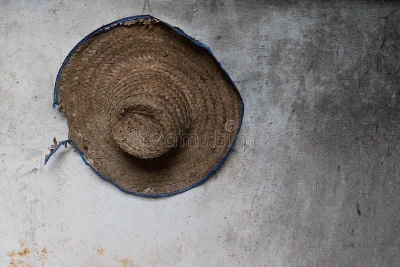 El sombrero de paja usado del granjero colgó en una pared imagenes de archivo