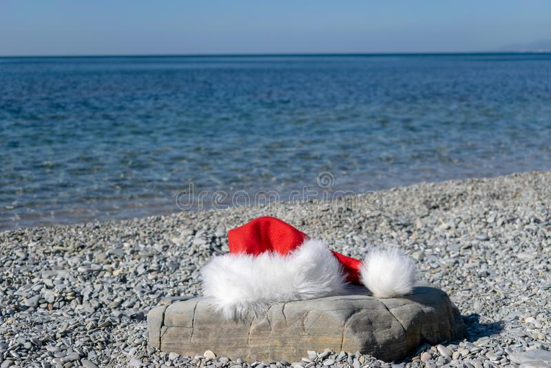 El sombrero de Santa Claus miente en una piedra grande en la costa Papá Noel fue a nadar fotos de archivo libres de regalías