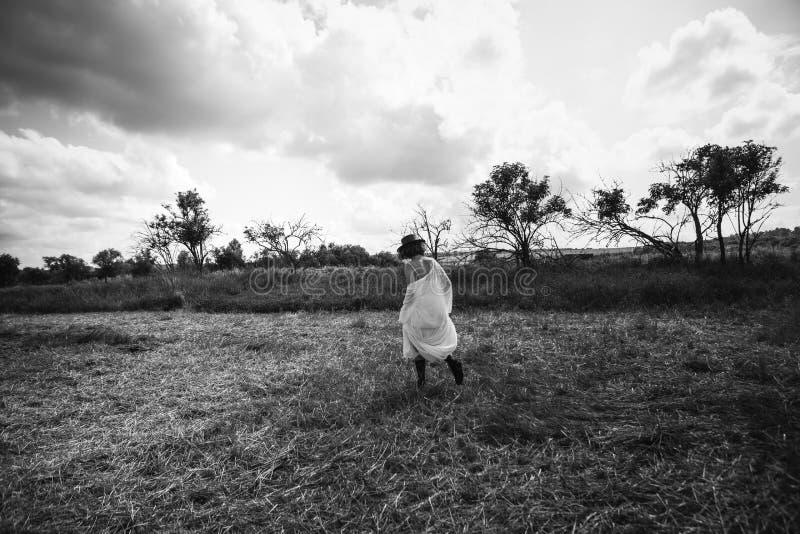 El sombrero de vestido forjado los paseos del campo del pueblo de la muchacha va fotos de archivo