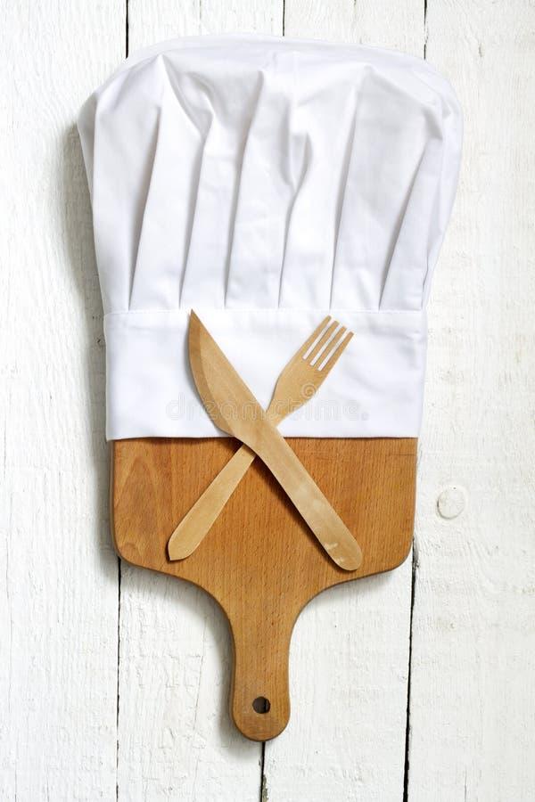 El sombrero del cocinero y la tabla de cortar vacía resumen el fondo de la comida imágenes de archivo libres de regalías