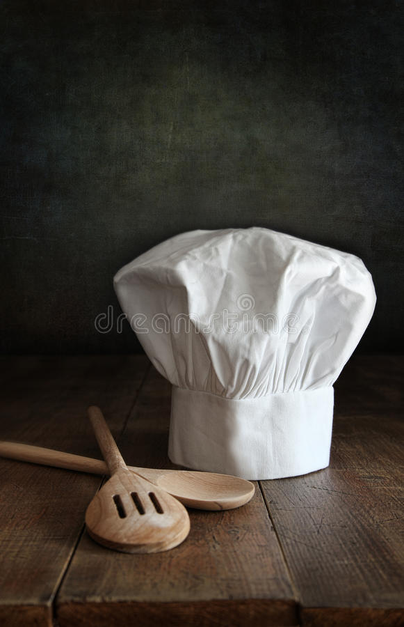 El sombrero del cocinero y wodden las cucharas en la madera fotos de archivo libres de regalías