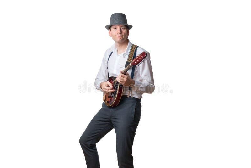 El sombrero que lleva del hombre se concentra que toca la mandolina imagen de archivo libre de regalías
