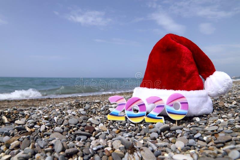 El sombrero rojo de Pap? Noel y los n?meros 2020 en el guijarro de la playa contra el mar azul fotos de archivo libres de regalías