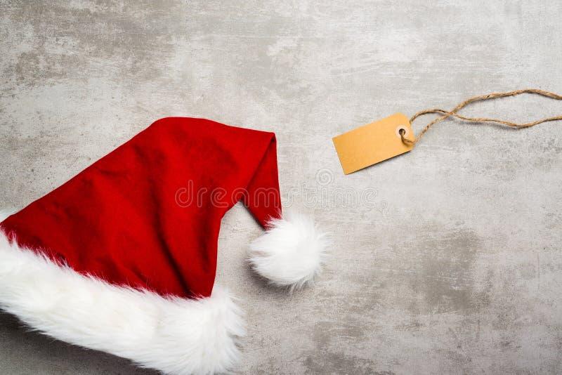 El sombrero rojo de santa y un regalo marcan con etiqueta en una tabla concreta gris fotografía de archivo