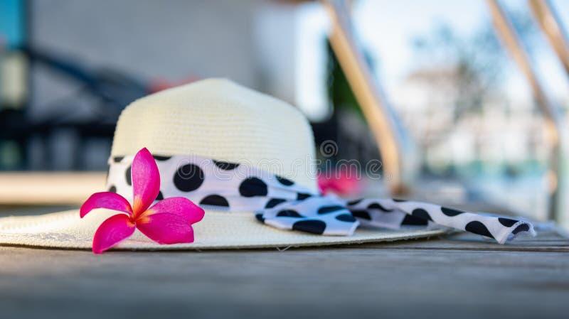 El sombrero y el frangipani del sol de la paja florecen en la terraza de nadar p fotos de archivo libres de regalías