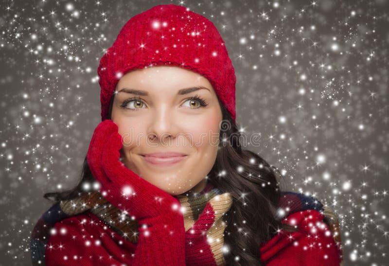 El sombrero y los guantes del invierno de la mujer contenta de la raza mixta que llevan disfruta de las nevadas fotografía de archivo libre de regalías