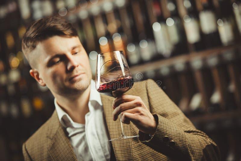 El Sommelier considera el vino tinto en bokal en el fondo de estantes con las botellas en sótano Color de apreciación masculino,  imagenes de archivo