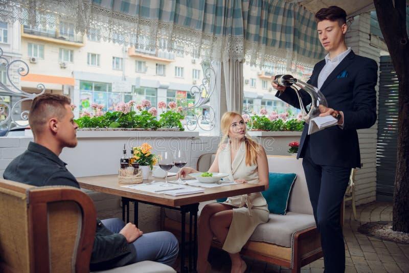 El sommelier vierte el vino en la jarra cerca de las huéspedes en el restaurante Fecha romántica Prueba de vino imagen de archivo