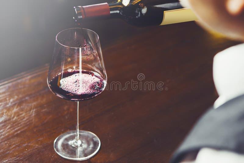 El Sommelier vierte el vino tinto a la copa en el fondo del contador de la barra, opinión del primer imagen de archivo libre de regalías