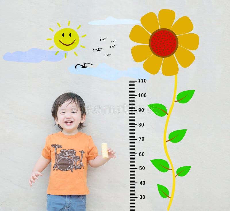 El soporte asiático feliz del niño del primer para la altura de la medida con el girasol lindo de la historieta en la pared de pi foto de archivo