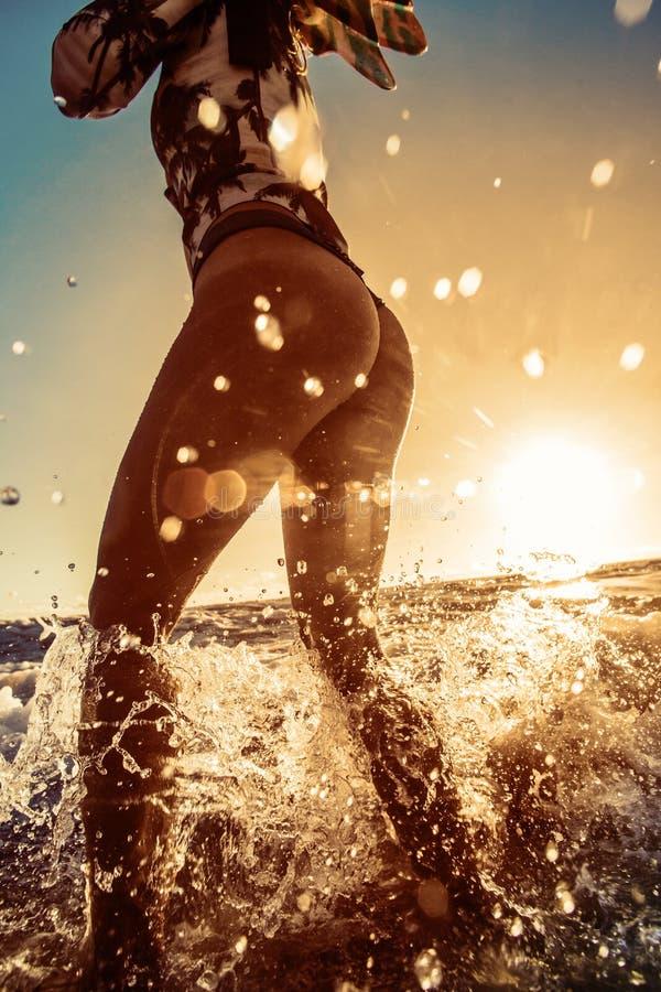 El soporte de la muchacha de la playa adentro salpica en agua foto de archivo libre de regalías