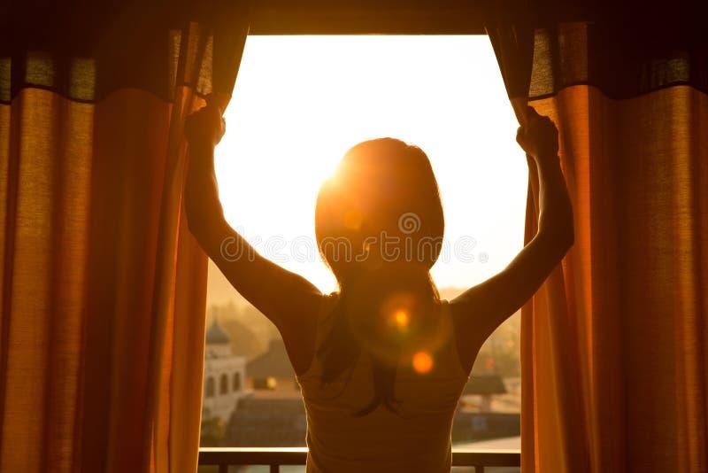 El soporte de la mujer en la cortina abierta del sitio considera salida del sol fotos de archivo