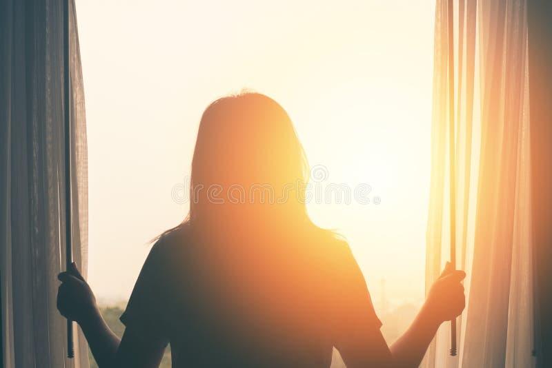El soporte de la mujer joven en la cortina abierta del dormitorio considera salida del sol después de despertar imagen de archivo