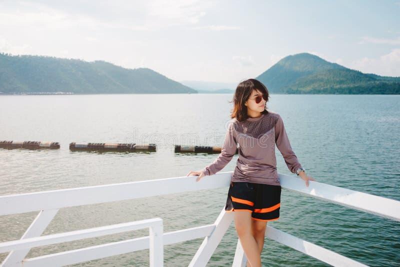 El soporte de la mujer joven solamente en el frente del balcón de ella tiene mar, mountai imagen de archivo