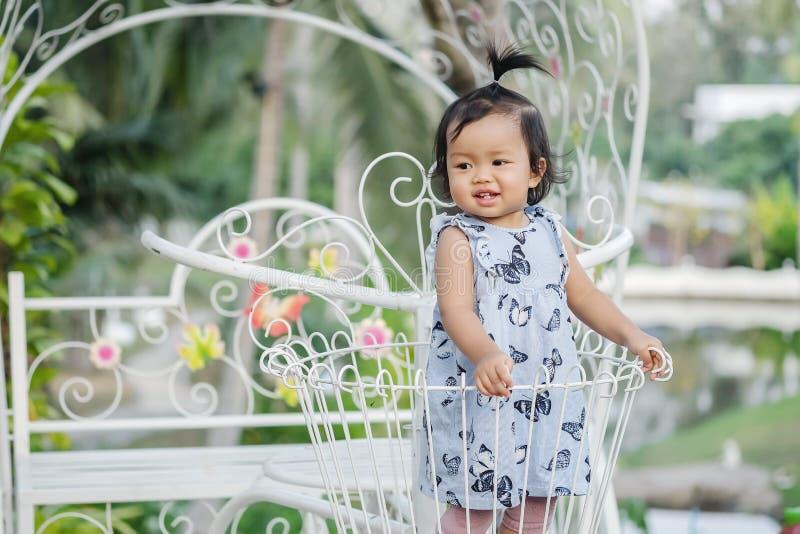 El soporte de la niña del primer en la cesta de acero de la bicicleta para adorna en el fondo del jardín con la cara de la sonris imágenes de archivo libres de regalías