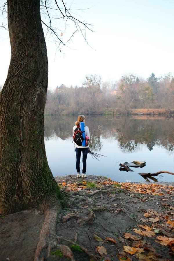 El soporte del caminante de la mujer y se relaja en el riverbank foto de archivo