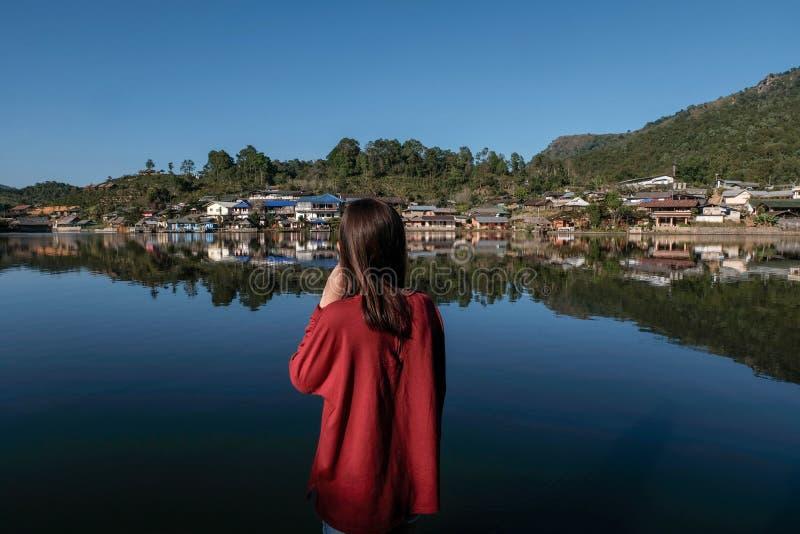 el soporte del viajero de las mujeres de Asia cerca refleja el lago que mira hacia fuera para ver de casa vieja y para tocar su p imagen de archivo