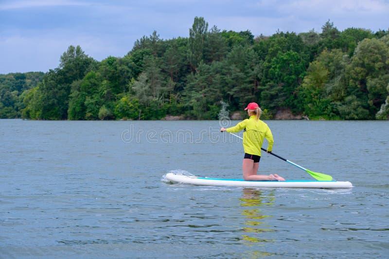 El SORBO se levanta el concepto del tablero de paleta - bonito, embarque de paleta de la mujer joven en un lago imagen de archivo