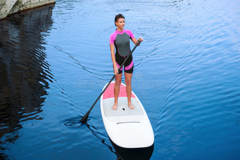 El SORBO se levanta a la mujer del tablero de paleta paddleboarding imagenes de archivo