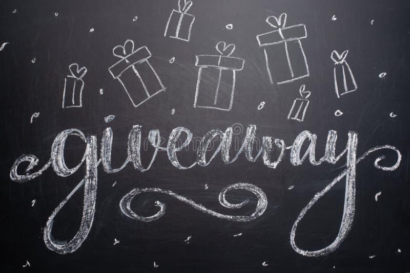 El sorteo de la inscripción se escribe en una pizarra con los regalos Distribución de regalos Blog, bloggers, redes sociales, ins fotos de archivo