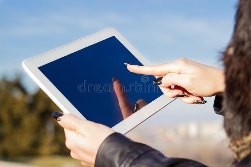El sostenerse de la mano de la mujer y PC digital conmovedora de la tableta imagen de archivo