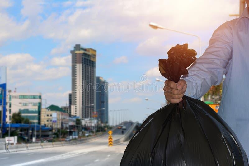 El sostenerse negro del bolso de basura a disposición del hombre fotos de archivo