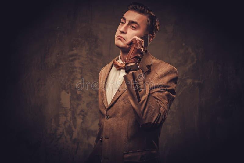 El sostenido vistió al hombre con la chaqueta que llevaba y la corbata de lazo del teléfono móvil fotografía de archivo