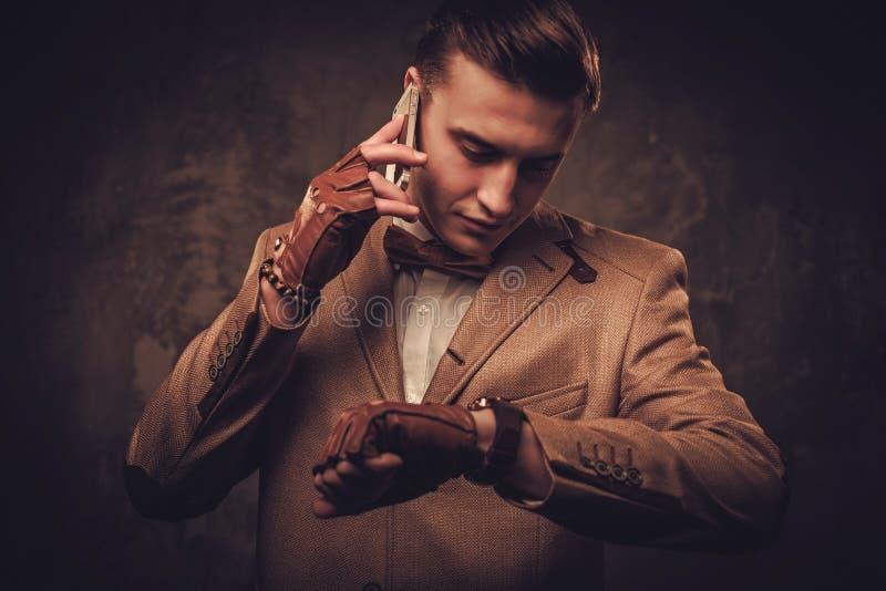 El sostenido vistió al hombre con la chaqueta que llevaba y la corbata de lazo del teléfono móvil foto de archivo