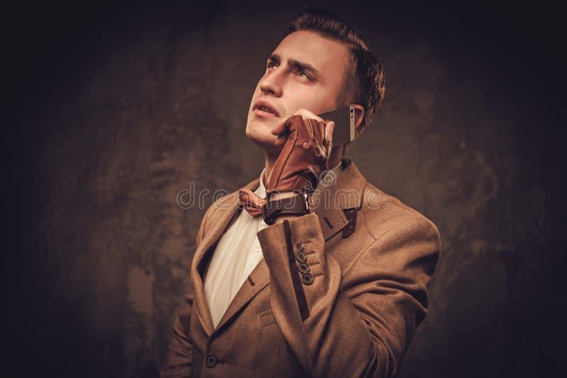 El sostenido vistió al hombre con la chaqueta que llevaba y la corbata de lazo del teléfono móvil imagen de archivo libre de regalías