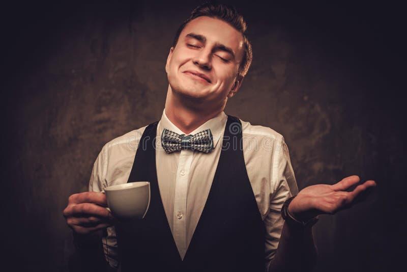 El sostenido vistió el chaleco que llevaba del hombre con una taza de café fotografía de archivo libre de regalías