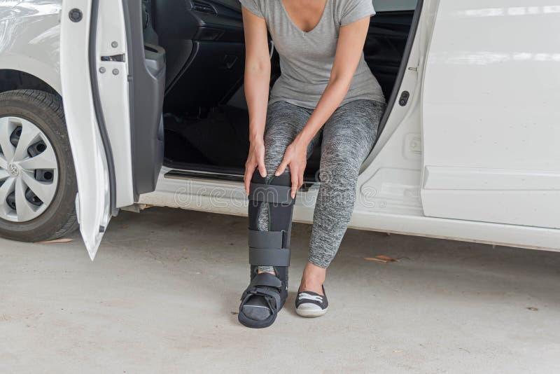 el sportsware que llevaba injurred de la mujer con negro echó en sittin de la pierna fotos de archivo