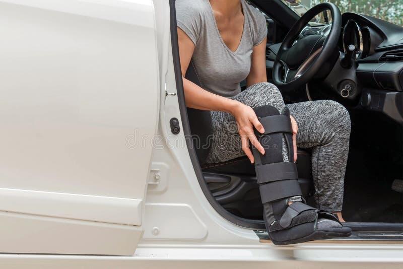 el sportsware que llevaba injurred de la mujer con negro echó en sittin de la pierna imagen de archivo libre de regalías