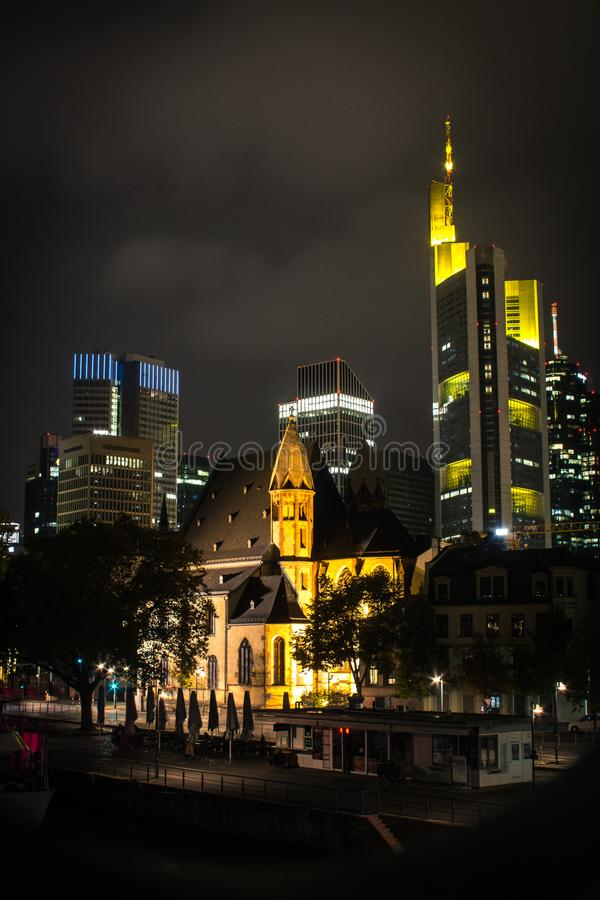 El St Leonhard es una iglesia católica y una parroquia en Frankfurt-am-Main, rodeada por los rascacielos en la noche alemania imagenes de archivo