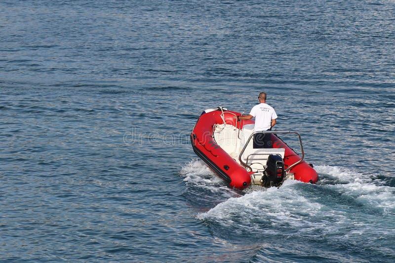 El staf del puerto deportivo est? navegando en una motora inflable roja a un yate navegante de la traves?a que entra en el puerto fotografía de archivo