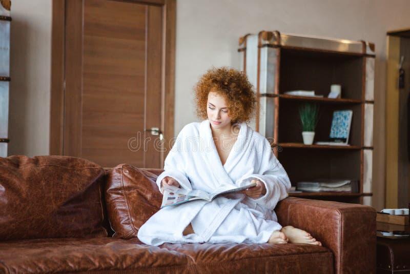 El stting femenino relajado encantador en el sofá y lectura de la revista de moda fotos de archivo