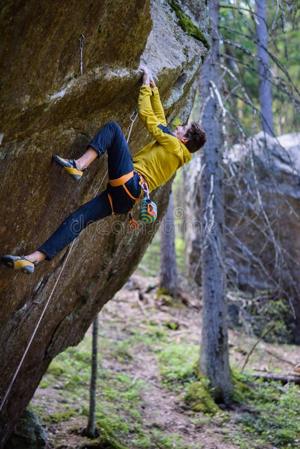 El subir extremo del deporte Escalador de roca que asciende un cli desafiador fotografía de archivo