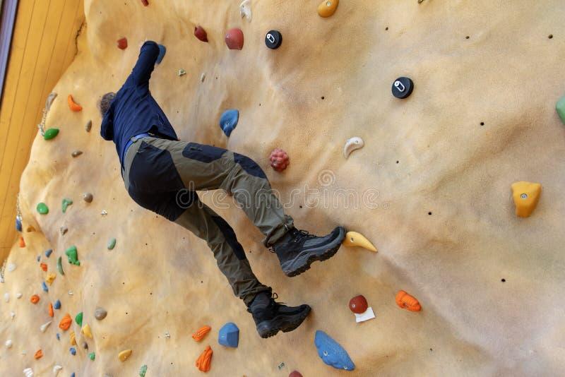 El subir practicante del escalador libre en la pared artificial al aire libre de la roca foto de archivo