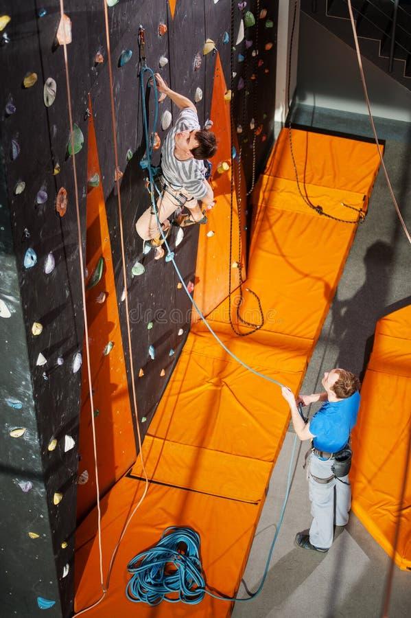 El subir practicante del roca-escalador masculino en la pared de la roca dentro imagenes de archivo