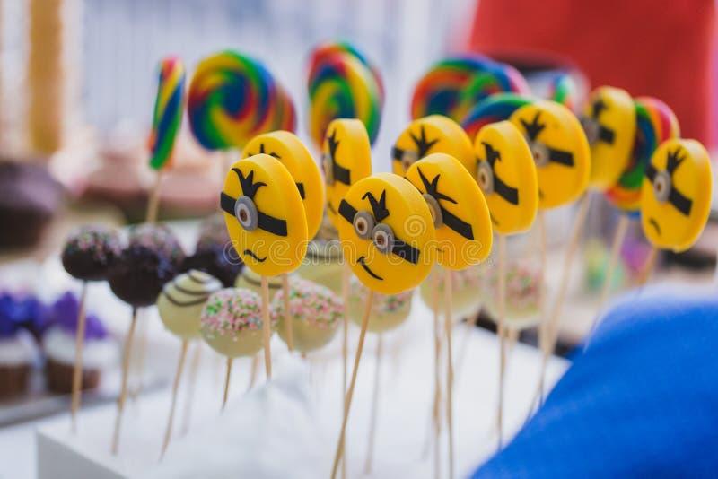 El subordinado amarillo hace frente a los lollypops, caramelo divertido del palillo, exhibición de la escuela para los niños imagenes de archivo