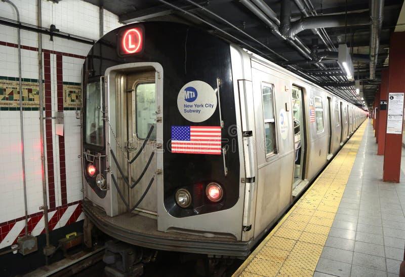 El subterráneo L tren de NYC llega la octava estación de la avenida en Manhattan imagenes de archivo