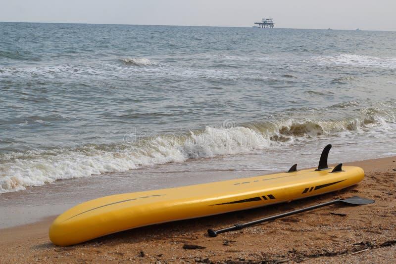 El supboard amarillo miente en la playa arenosa al lado de la paleta fotografía de archivo libre de regalías